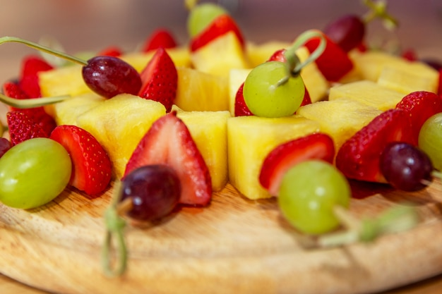 Appetitliche fruchtkanapees aus erdbeeren, ananas und trauben auf einem holzbrett. nahansicht. snacks vom buffet.