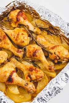 Appetitliche hähnchenschenkel mit kartoffeln und rosmarin in folie gebacken.