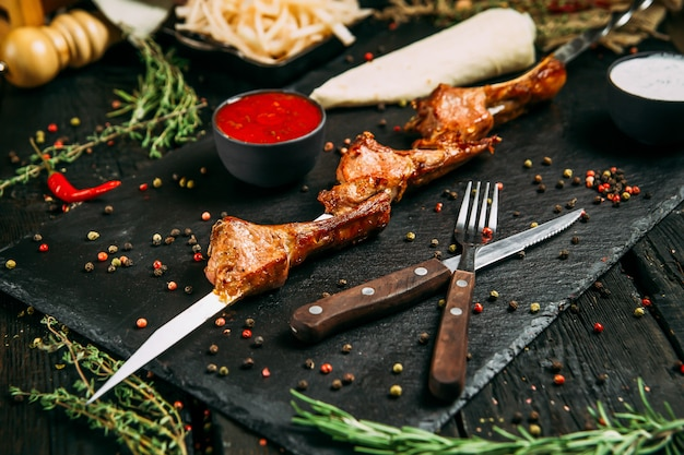 Appetitliche hammel-entrecote-spieße mit roter sauce und eingelegten zwiebeln auf einem schwarzen brett