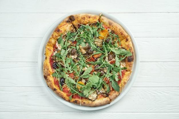 Appetitliche hausgemachte gemüsepizza mit oliven, geschmolzenem käse, rucola, pilzen, kirschtomaten auf einem weißen