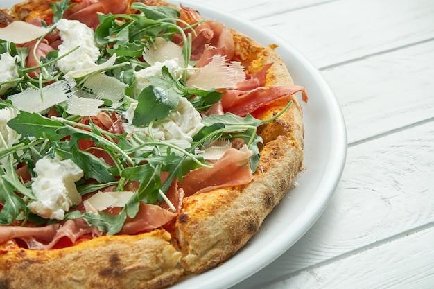 Appetitliche hausgemachte pizza mit jamon, parmesan, rucola und straccella auf einem weißen teller auf einem weißen