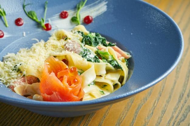 Appetitliche, hausgemachte tagliatelle-nudeln mit spinat und lachs, parmesan in einer blauen schüssel auf einer holzoberfläche. italienische küche. fügen sie lärm auf dem post hinzu. selektiver fokus
