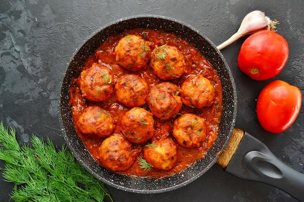Appetitliche hühnerfleischbällchen in tomatensauce. fleischbällchen in einer pfanne auf einem dunklen tisch. hühnerschnitzel in tomaten. fleischgericht.