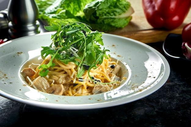 Appetitliche italienische pasta mit waldpilzen und weißer sauce, serviert in einem weißen teller auf einem dunklen marmortisch. italienische spaghetti. restaurant essen