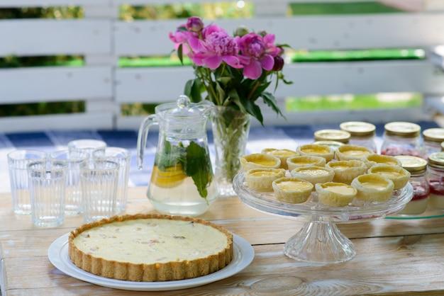 Appetitliche kuchen und limonade werden auf einem weißen hölzernen picknicktisch mit einer vase mit pfingstrosenblüten gekocht. sommer familienurlaub. picknick.