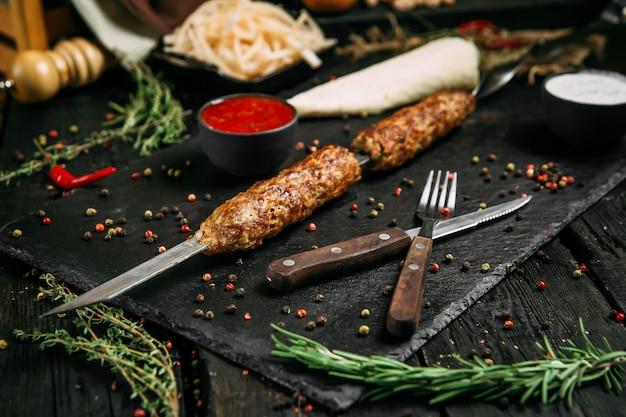 Appetitliche lula-spieße mit roter sauce und eingelegten zwiebeln auf einem schwarzen brett