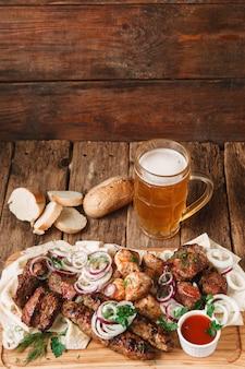 Appetitliche mahlzeit in der kneipe mit frisch gegrilltem fleischsortiment, pittabrot, brötchen und einem becher kaltem hellem bier, serviert auf holzoberfläche.