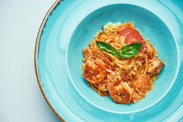 Appetitliche nudeln mit tomaten und garnelen, parmesan in einer blauen schüssel auf einer grauen oberfläche. italienische küche