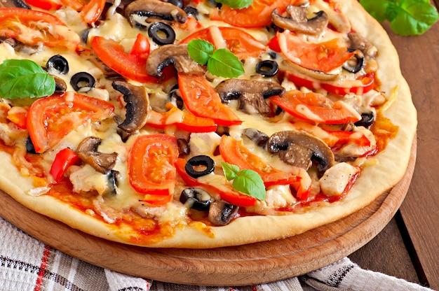 Appetitliche pizza mit hähnchen, tomaten, paprika und champignons