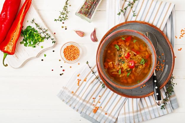 Appetitliche suppe mit roten linsen, fleisch, rotem paprika und duftendem thymian. flach liegen. ansicht von oben
