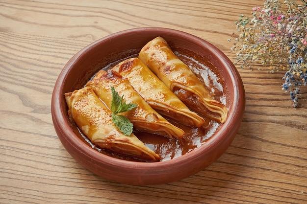 Appetitliche und saftige pfannkuchen mit apfelmarmelade und zimt in einer braunen schüssel auf einem holztisch. französische crepes