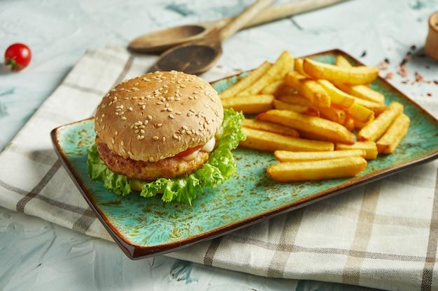 Appetitlicher burger mit hühnerschnitzel, tomaten, mozzarella und salat mit einer beilage aus pommes frites auf einem keramikteller. fast food. nahansicht