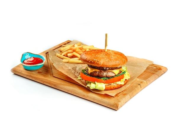 Appetitlicher burger mit pommes liegt auf einem holzbrett, serviert mit roter sauce isoliert