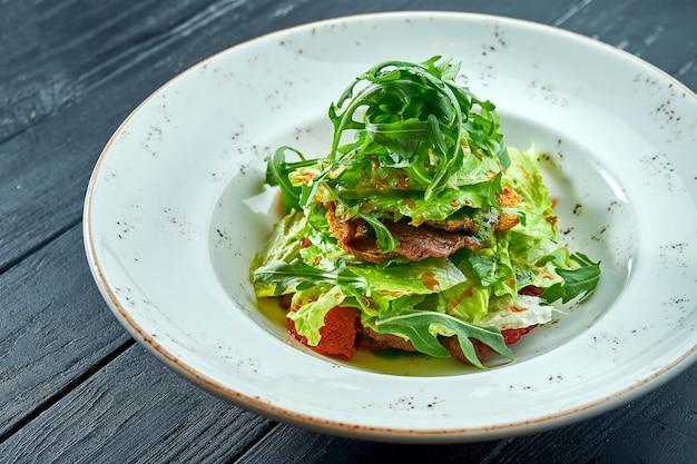 Appetitlicher, diätetischer salat mit rucola, sauce, salat und warmem rindfleisch in einem weißen teller auf dunklem holztisch