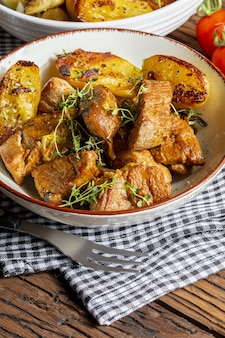 Appetitlicher eintopf vom im wok gebratenen schweinefilet in würfel geschnitten mit gerösteten und goldenen kartoffeln hausgemachter look