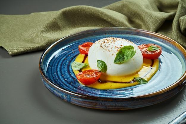 Appetitlicher italienischer burrata-käse mit mozzarella mit pfirsichcreme auf einem blauen teller auf einem holztisch. luxus restaurant essen. nahaufnahme, speicherplatz kopieren