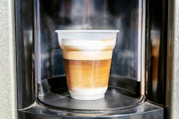 Appetitlicher kaffee in einer plastikschale von der maschine. nahansicht.