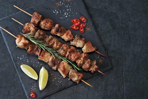 Appetitlicher kebab mit gewürzen, chili und limette. wohlriechende schweinefleischaufsteckspindeln auf einem steinbrett.