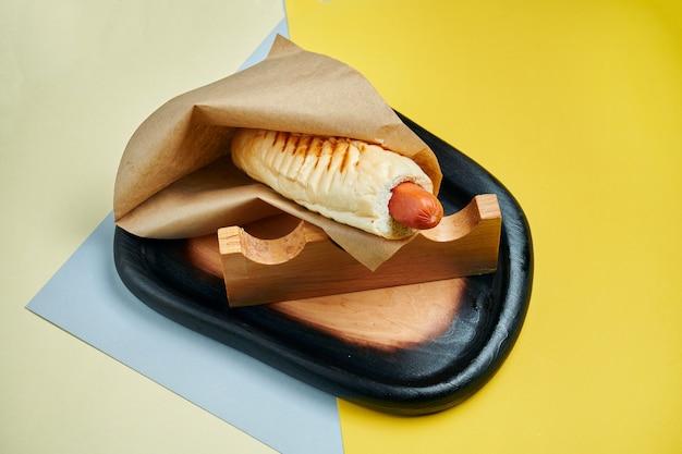 Appetitlicher klassischer amerikanischer hot dog mit karamellisierten zwiebeln, cheddar-käse, senf und ketchup mit einer beilage aus kartoffeln auf einer farbigen oberfläche fast food