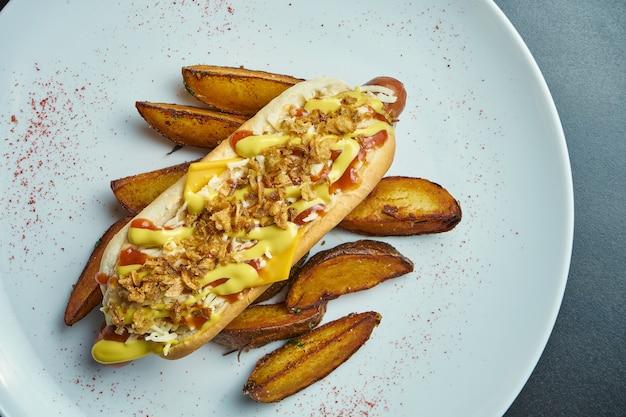 Appetitlicher klassischer amerikanischer hot dog mit karamellisierten zwiebeln, cheddar-käse, senf und ketchup mit einer beilage aus kartoffeln. fast food