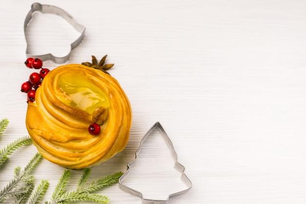 Appetitlicher muffin mit festlichen weihnachtsdekorationen, backgeschirr auf weißem holztisch Premium Fotos