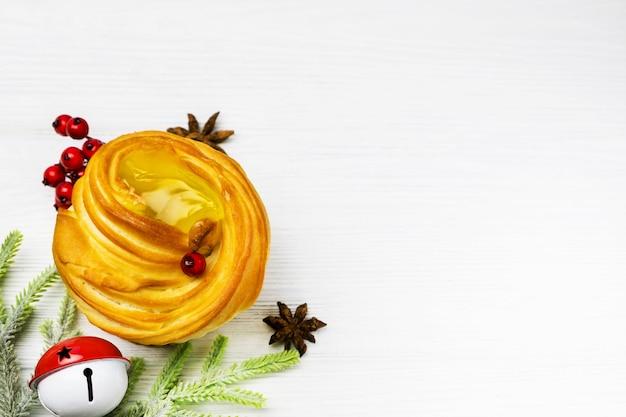 Appetitlicher muffin mit festlichen weihnachtsdekorationen, backgeschirr auf weißem holztisch