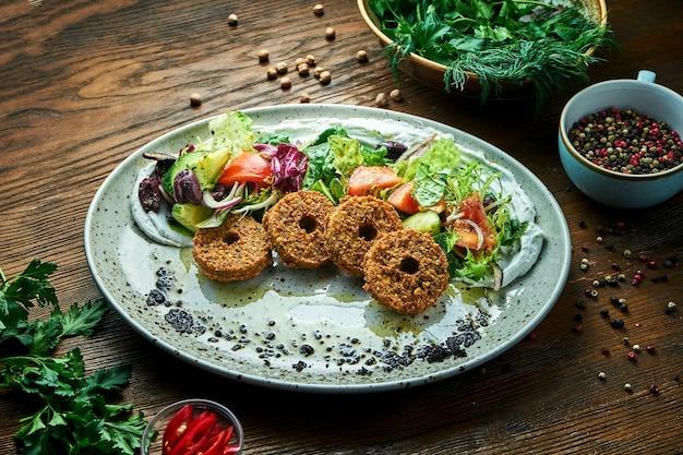 Appetitlicher salat im stil der orientalischen küche. frischer gemüsesalat mit falafel und olivenöl serviert in einem blauen teller auf einem holztisch. restaurant essen