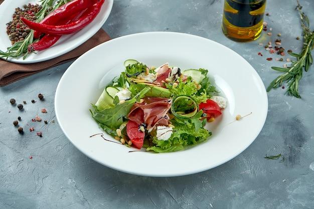 Appetitlicher salat mit jamon, feta-käse, avocado in einem weißen teller