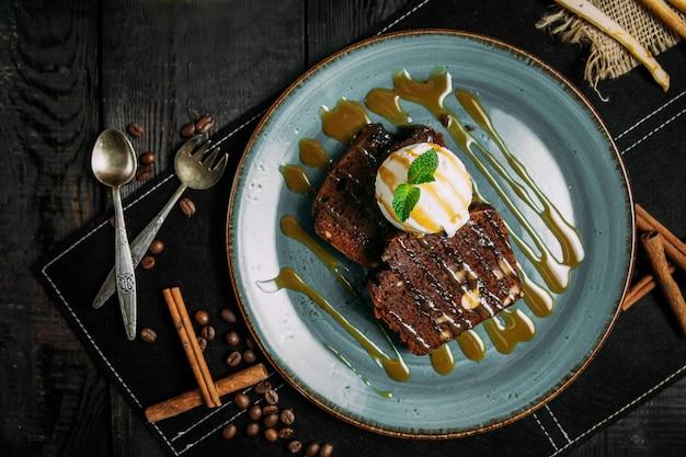 Appetitlicher schokoladen-brownie mit vanilleeis auf einem teller auf dem holztisch mit dekorationselementen, horizontal