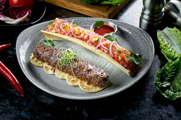 Appetitlicher türkischer lamm-lula-kebab mit tomatentartar und roter sauce, serviert in einem grauen teller. dunkler marmortisch. grillfleisch, restaurantessen.