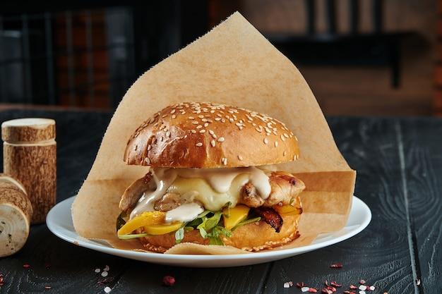 Appetitlicher und saftiger burger mit gegrillter hähnchenbrust, rucola, paprika, geschmolzenem camembertkäse und weißer sauce auf einem weißen teller mit pommes frites. nahansicht