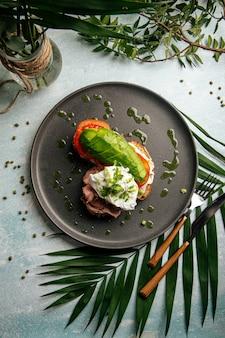 Appetitliches avocado-sandwich mit roastbeef und pochiertem ei zum frühstück