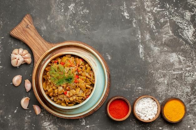 Appetitliches gericht drei gewürze knoblauch neben den appetitlichen grünen bohnen und tomaten auf dem schneidebrett auf dem schwarzen tisch