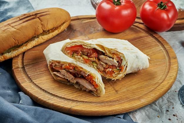 Appetitliches shaurma oder shawerma mit fleisch, tomate, kohl. hühnerfleisch. kebab auf holztablett. nahaufnahme, selektiver fokus