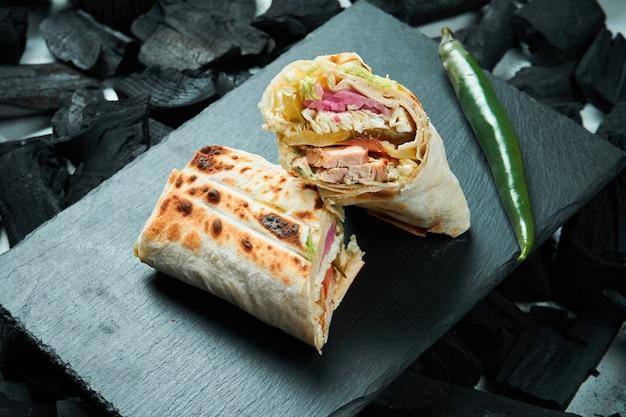 Appetitliches shaurma oder shawerma mit gewürzen und zwiebeln auf einem schwarzen schiefertablett auf einem tisch aus holzkohle. kebab