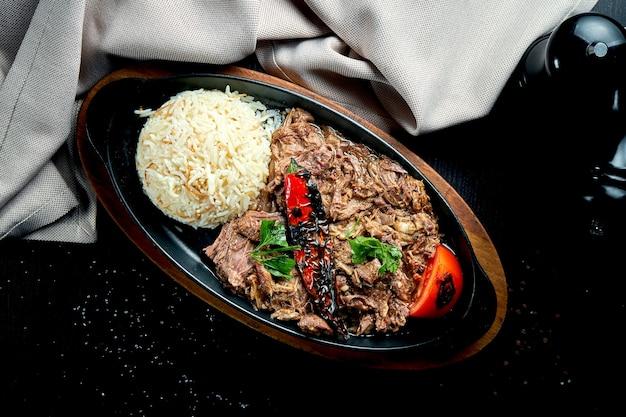 Appetitliches türkisches gericht - im ofen gebackenes lammfleisch mit gegrilltem gemüse und reis in einer schwarzen pfanne auf einem schwarzen tisch