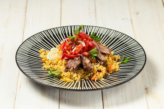 Appetitliches usbekisches gericht mit reis und fleisch