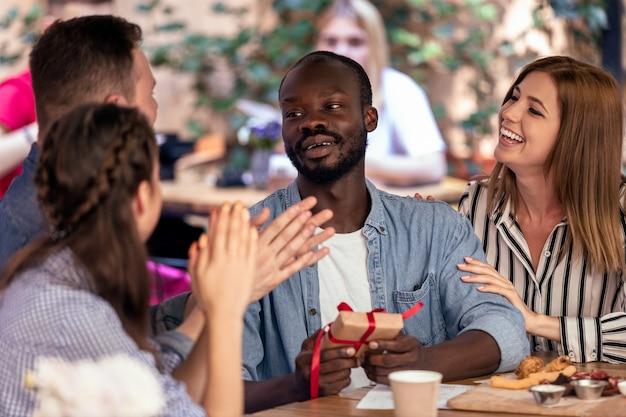 Applaus und geschenke für einen afrikanischen jungen von seinen kaukasischen freunden am gemütlichen café