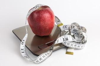 Apple auf Waage und messendem Band mit weißem Hintergrund