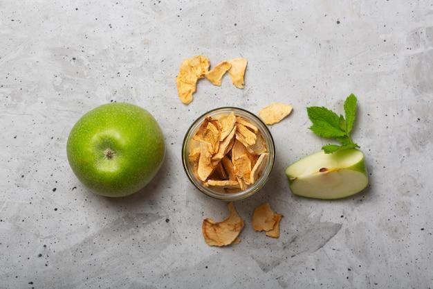 Apple bricht in einem glas und in stücken dieser früchte auf einer tabelle ab