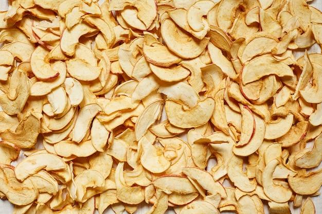 Apple-chips auf der gesamten oberfläche des tisches. vegetarische diät. getrocknete apfelscheiben.
