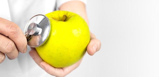 Apple in der hand des ernährungswissenschaftlers mit stethoskop, nahaufnahme. gesundheit in ihren händen. das konzept des diätvergleichs.