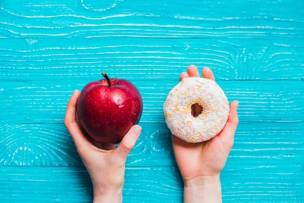 Apple und donut auf blauem holztisch