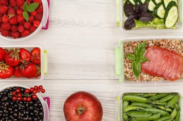 Apple- und meal prep-behälter mit frischen erdbeeren, himbeeren, gekochtem buchweizenbrei