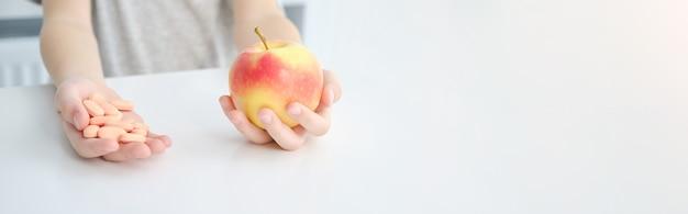 Apple und pillen in den händen. konzept der natürlichen vitamine.