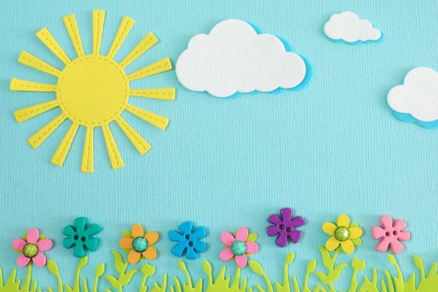 Applique gelbe sonne, wolken, üppiges grünes gras und helle mehrfarbige blumen auf blauem hintergrund.