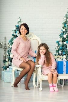 Appy-familienmutter und kindertochter am weihnachtsmorgen am weihnachtsbaum mit geschenken.