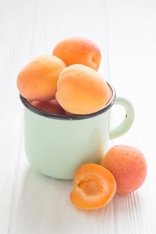Aprikose in der teeschale auf einem weißen holztisch