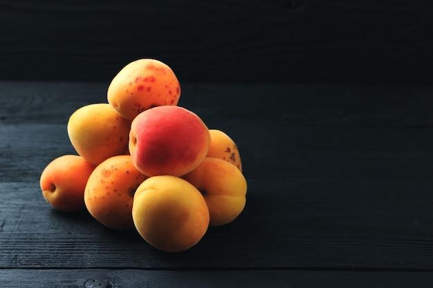Aprikosen auf schwarzem hölzernem hintergrund