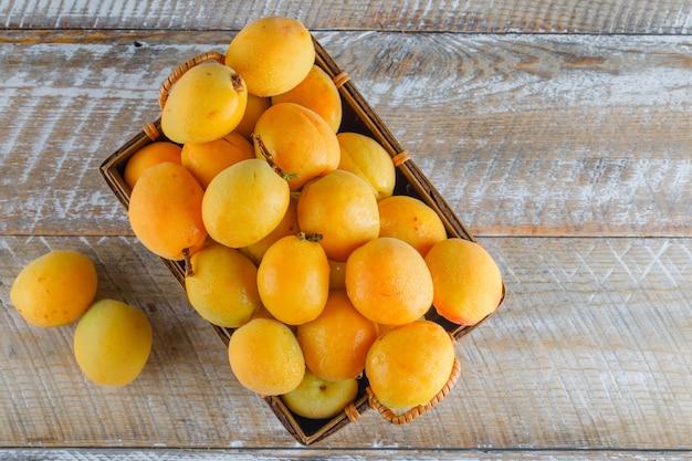 Aprikosen in einem korb auf holztisch, flach liegen.